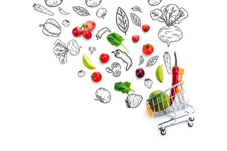 scattered fruits and vegetables with black and white illustration near decorative shopping cart isolated on white
