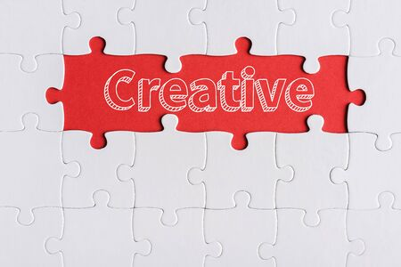 top view of connected jigsaw puzzle pieces near creative letters