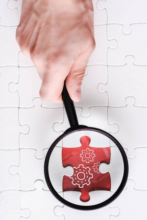 top view of man holding magnifying glass near jigsaw with gears settings near white connected puzzle pieces 写真素材