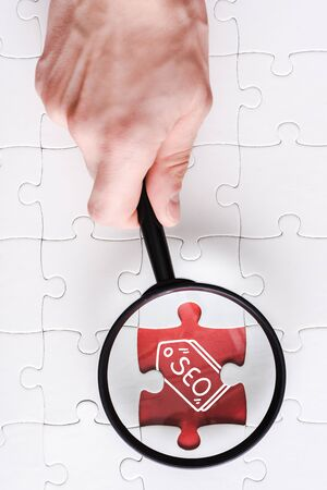 top view of man holding magnifying glass near jigsaw with seo lettering near white connected puzzle pieces