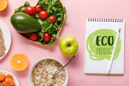 top view of fresh diet food and notebook with eco product lettering on pink background