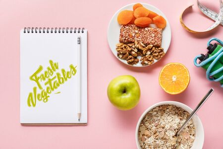 top view of fresh diet food, measuring tape, skipping rope and notebook with fresh vegetables lettering on pink background with copy space