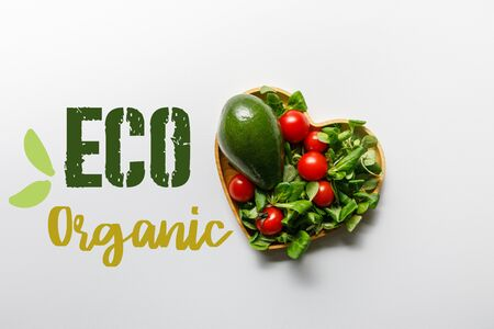 top view of fresh green vegetables in heart shaped bowl on white background with eco organic lettering