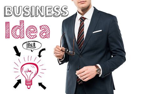 cropped view of businessman in suit holding glasses near business idea lettering on white