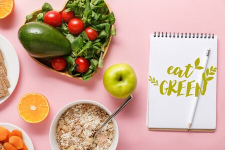 top view of fresh diet food and notebook with eat green lettering on pink background Reklamní fotografie