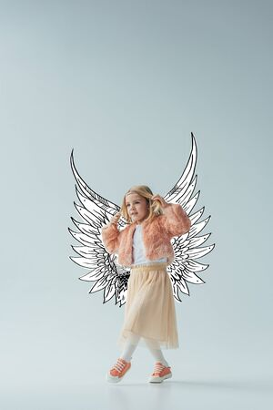 cute kid in faux fur coat and skirt with fairy angel wings walking and looking away on grey background Фото со стока