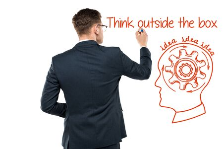 back view of businessman holding marker pen near think outside the box lettering on white