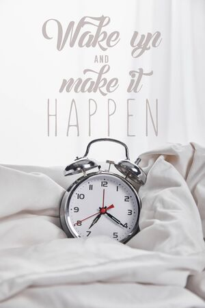 silver alarm clock in blanket in white bed with wake up and make it happen illustration Imagens - 130885168
