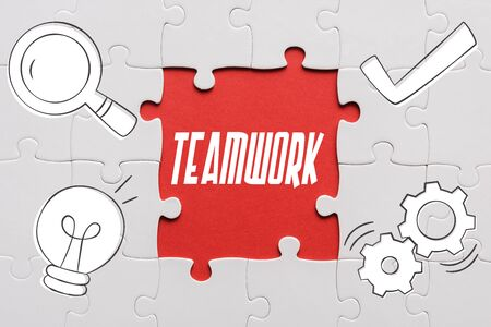 top view of connected jigsaw puzzle pieces near teamwork letters