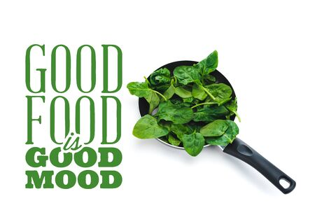 fresh spinach leaves in frying pan on white background near good food is good mood green lettering Reklamní fotografie