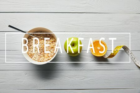 flat lay with breakfast cereal in bowl, apple, orange and measuring tape on wooden white background with breakfast lettering 写真素材