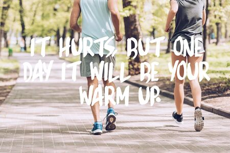 cropped shot of man in woman jogging together along walkway in park with it hurts, but one day it will be your warm up lettering