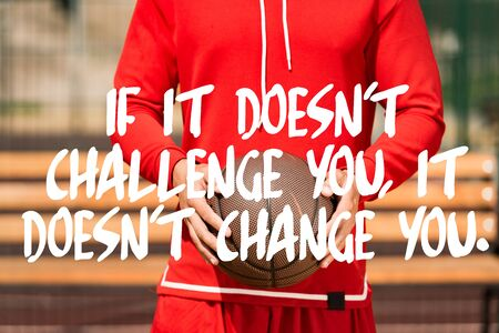 if it doesnt challenge you it doesnt change you lettering on partial view of basketball player holding ball