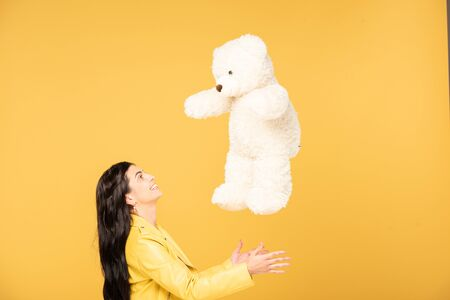 attractive cheerful woman throwing up teddy bear, Isolated On yellow Stock Photo