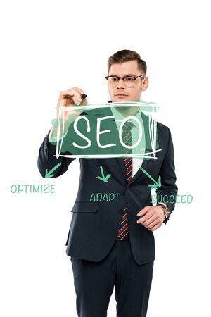 handsome businessman in glasses holding marker pen near seo lettering on white