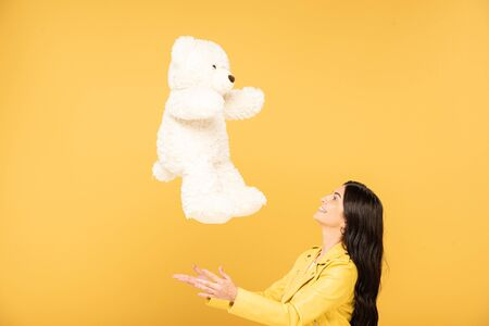 pretty young woman throwing up teddy bear, Isolated On yellow Stock Photo