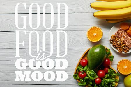 top view of fresh fruits, vegetables in heart-shaped bowl on wooden white background with good food is good mood lettering