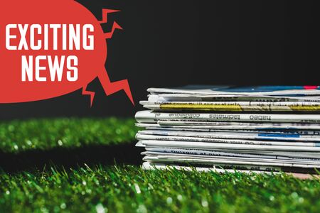 stack of different print newspapers on fresh green grass near red speech bubble with exciting news lettering isolated on black Stock Photo