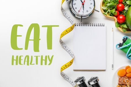 top view of sport equipment, measuring tape, alarm clock and diet food near empty notebook on white background with eat healthy lettering Reklamní fotografie - 130885287