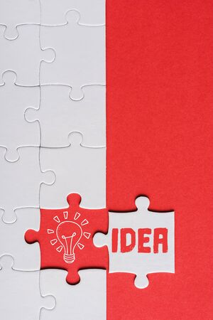 top view of incomplete jigsaw near white puzzle piece with idea lettering isolated on red