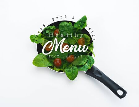 fresh spinach leaves and cherry tomatoes in frying pan with healthy menu lettering on white background Фото со стока