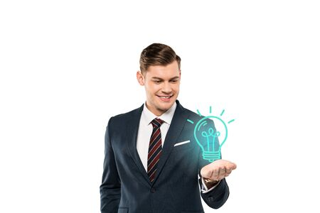 happy young man in formal wear gesturing and looking at light bulb on white