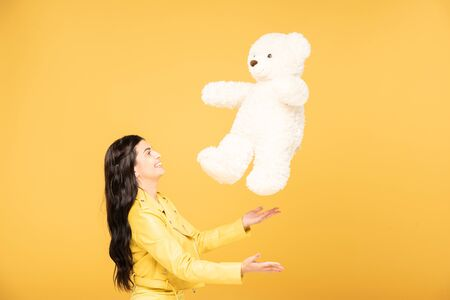 cheerful young woman throwing up teddy bear, Isolated On yellow