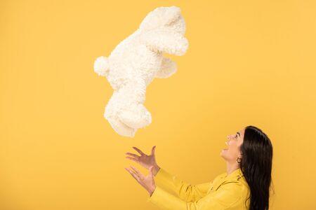 happy girl throwing up teddy bear, Isolated On yellow