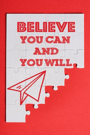 top view of white connected puzzle pieces with paper plane and believe you can and you will lettering isolated on red