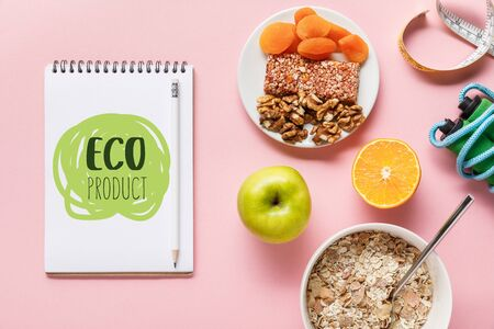 top view of fresh diet food, measuring tape, skipping rope and notebook with eco product lettering on pink background Imagens - 130885765