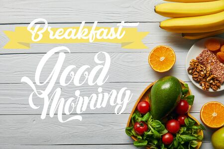 top view of fresh fruits, vegetables in heart-shaped bowl on wooden white background with breakfast, good morning lettering Stockfoto
