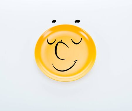 top view of shiny yellow plate with pleased smiley on white background