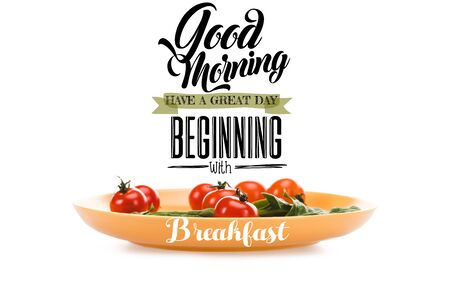 cherry tomatoes with green spinach leaves in yellow plate with good morning, have a great day beginning with breakfast lettering above isolated on white Фото со стока