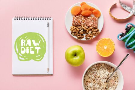 top view of fresh diet food, measuring tape, skipping rope and notebook with raw diet lettering on pink background with copy space