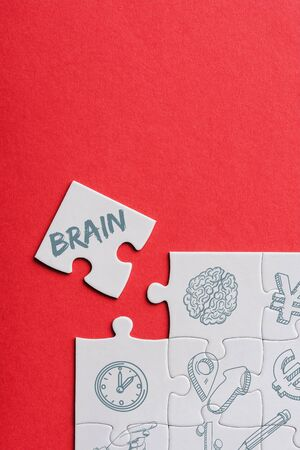 top view of unfinished white puzzles near separate piece with brain lettering isolated on red Stok Fotoğraf - 130886137