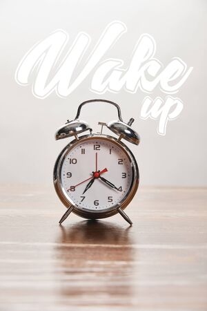 silver alarm clock on wooden table isolated on grey with wake up illustration Stock Photo