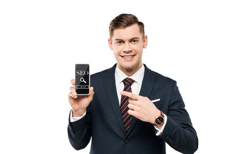 happy businessman in suit pointing with finger at smartphone with seo lettering on screen  isolated on white