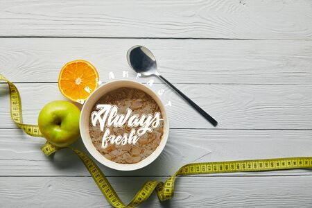top view of measuring tape, spoon and breakfast cereal in bowl near apple and orange on wooden white background with breakfast always fresh lettering Reklamní fotografie