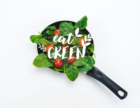 fresh spinach leaves and cherry tomatoes in frying pan with eat green lettering on white background Imagens