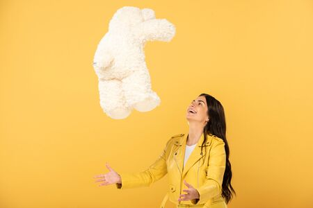 beautiful brunette girl throwing up teddy bear, Isolated On yellow Stock Photo