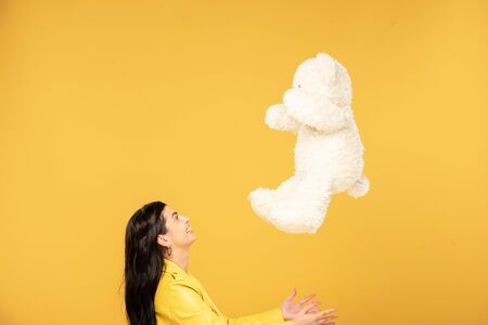 beautiful young woman throwing up teddy bear, Isolated On yellow