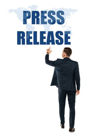back view of man pointing with finger at press release lettering while standing on white Stock Photo