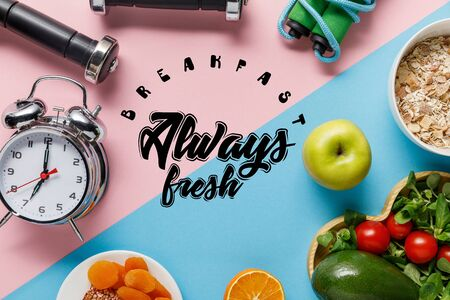 top view of delicious diet food and sport equipment with alarm clock on blue and pink background with breakfast always fresh lettering