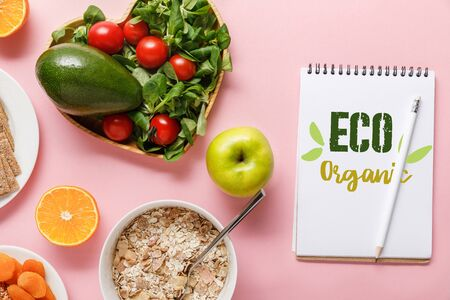 top view of fresh diet food and notebook with eco organic words on pink background