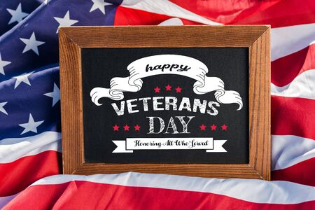 chalkboard with happy veterans day, honoring all who served illustration on american flag with stars and stripes