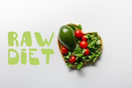top view of fresh green vegetables in heart shaped bowl on white background with raw diet lettering