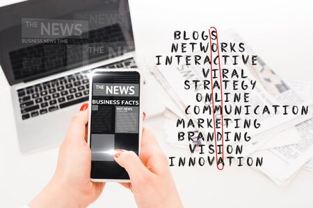 selective focus of woman holding smartphone with business news illustration near laptop, newspapers and social media crossword Фото со стока