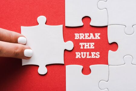 top view of woman touching jigsaw near break the rules lettering and connected white puzzle pieces and idea lettering on red