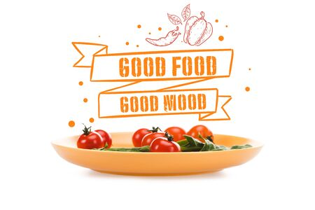 cherry tomatoes with green spinach leaves in yellow plate with good food good mood lettering above isolated on white