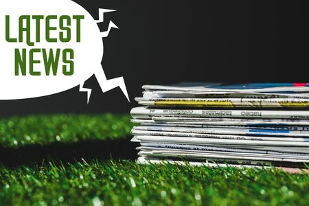 stack of different print newspapers on fresh green grass near speech bubble with green latest news lettering isolated on black Stock Photo